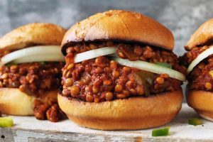 vegan sloppy joes with lentils and onion rings in buns on wooden surface