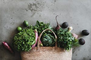 textile grocery bad laying on a wooden surface with fresh produce such as leafy greens, herbs, avocado, broccoli and aubergine