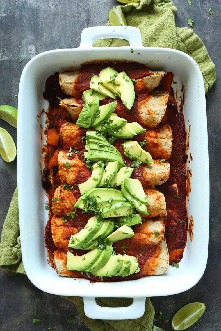 white baking dish on a green towel with homemade vegan butternut enchiladas topped with avocado