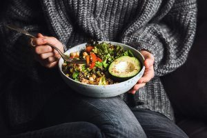 woman wearing jeans and a cozy knitted grey sweater having a ceramic bowl with greens, bell pepper, grains, beans and avocado on her lap