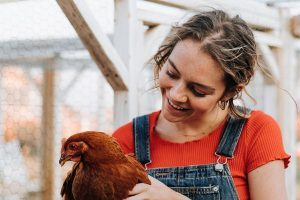 freckled woman with ponytail in red shirt and jeans holding a brown feathered chicken and smiling