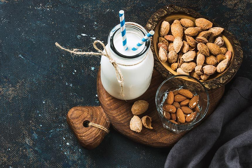 glass bottle with homemade almond milk and two paper straws next to some almonds on a wooden chopping board