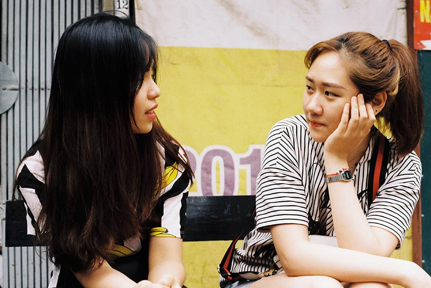 two young asian women sitting on a bench and talking with each other