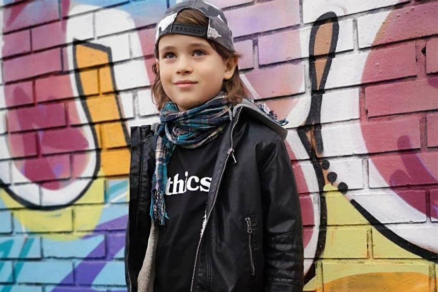 young vegan boy dressed in a black jacket and black shirt saying ethics in front of a colorful wall