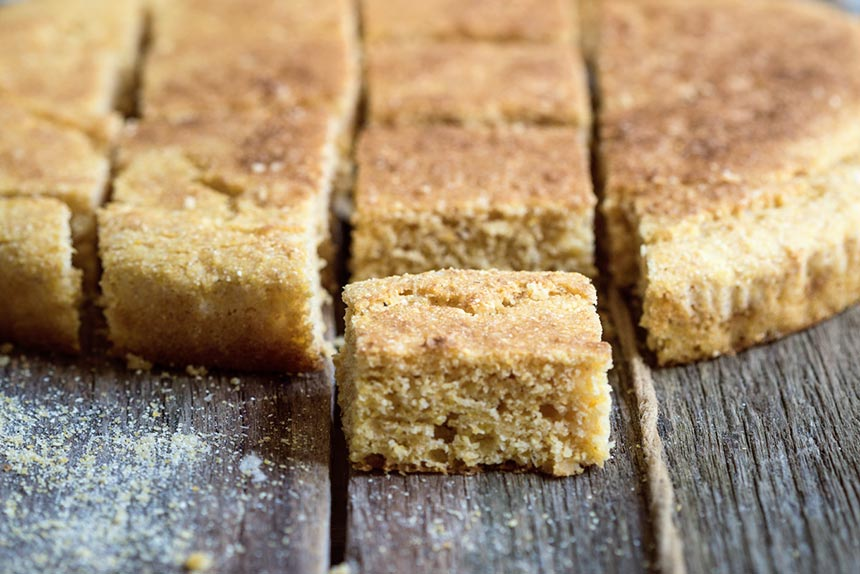 slices of vegan corn bread on a wooden table