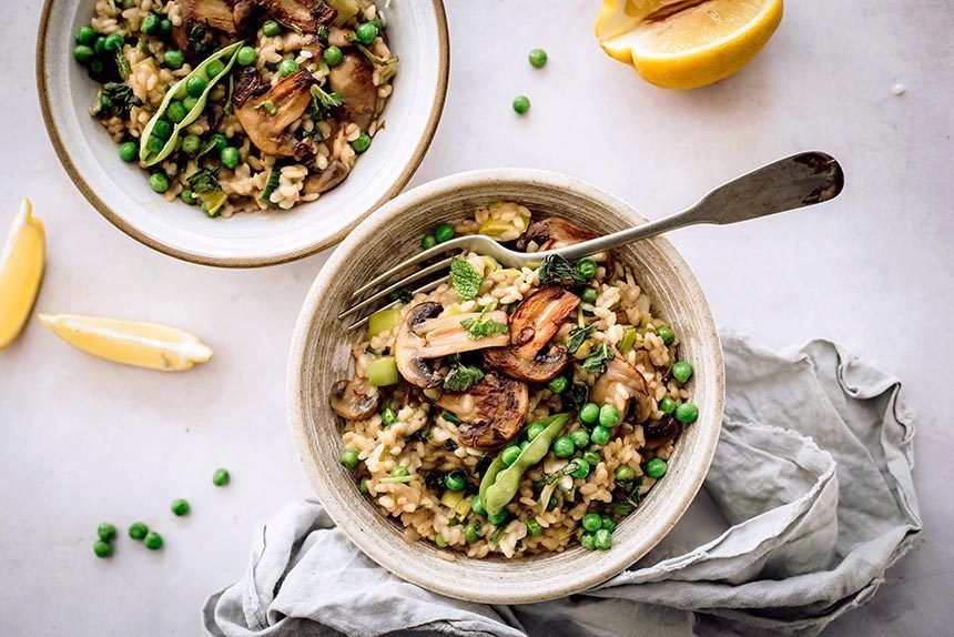 bowl of vegan risotto with mushroom, peas and a fork standing next to a linen on a marble surface