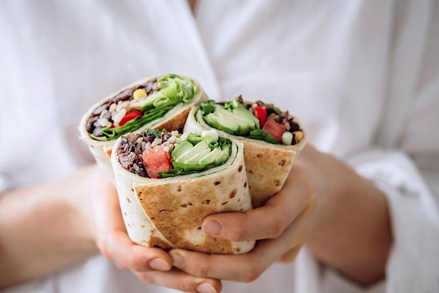 woman in white shirt holding three vegan bean burritos with fresh avocado and tomatoes
