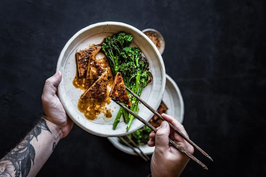 tattooed man holding a ceramic plate of roasted broccoli with marinated tofu of which one piece is between the chopping sticks he's holding