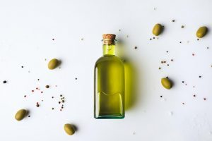 glass bottle of olive oil lying on a white surface next to some olives and pepper