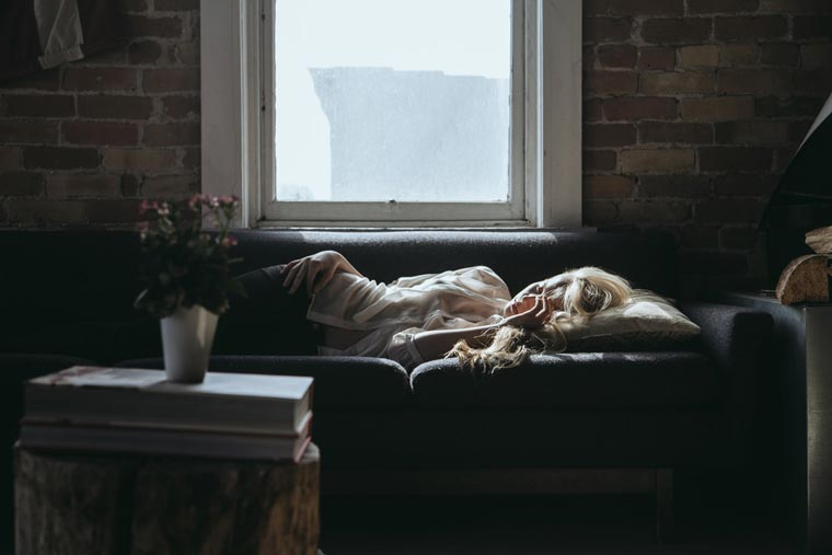 woman feeling sick, lying on couch