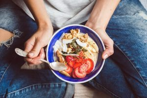 woman in jeans sitting cross-legged with a blue bowl of grains, strawberries, coconut, walnut and pumpkin seeds