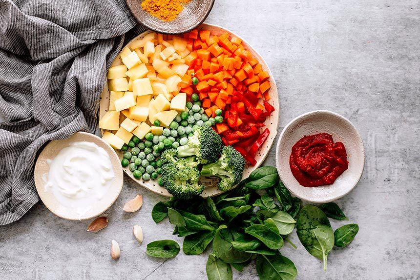 plate with potato, carrot, bell pepper, broccoli and peas standing next to small bowls of soy yogurt, spices, tomato paste and fresh spinach