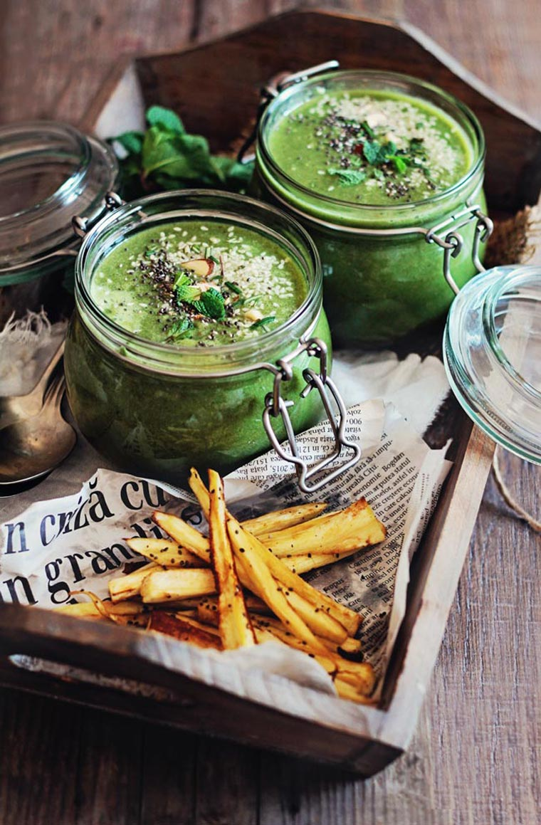 wooden tray with newspaper and sliced baked parsnip fries as well as two glass jars with green soup