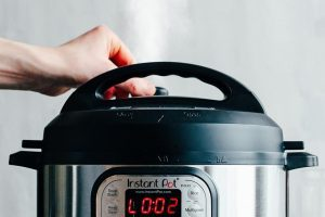 the electric pressure cooker instant pot being ready to release steam by hand moving the valve