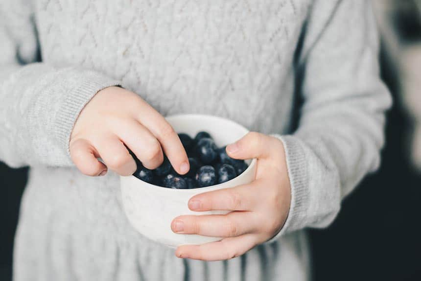 woman in grey dress mindfully eating blueberries out of a white bowl