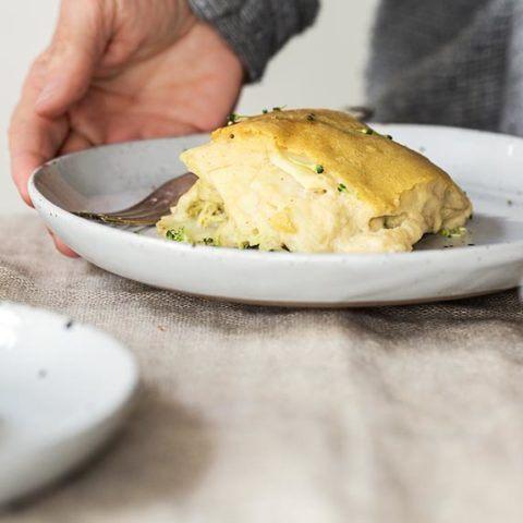 piece of vegan broccoli potato casserole on a white plate standing on some linen