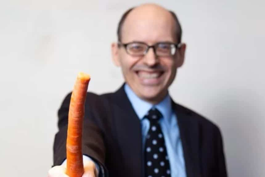 Vegan doctor Michael Greger standing with a carrot in his hand and smiling