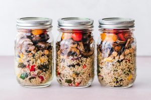 three mason jars with meal prepped vegan salad consisting of quinoa, mushrooms, tomatoes, corn and chopped veggies