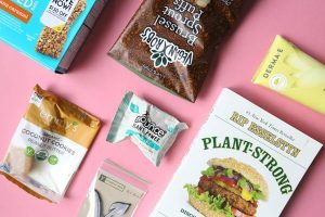 7 kinds of different vegan packaged snacks lying on pink surface