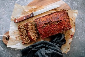 hearty vegan lentil loaf with red glaze on some parchment paper on a wooden chopping board