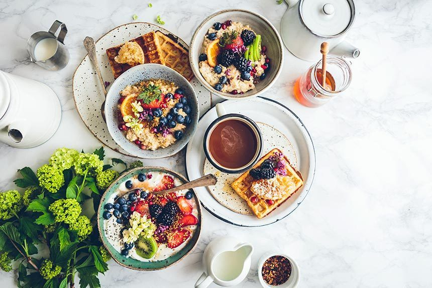 marble table with some flowers and lots of bright bowls filled with colorful vegan waffles and oatmeal with fruit