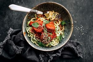 vegan black bean balls in marinara sauce with zucchini noodles and a fork in a dark bowl