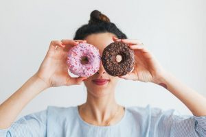 woman with bun craving junk food and holding a brown and a pink doughnut in front of her face