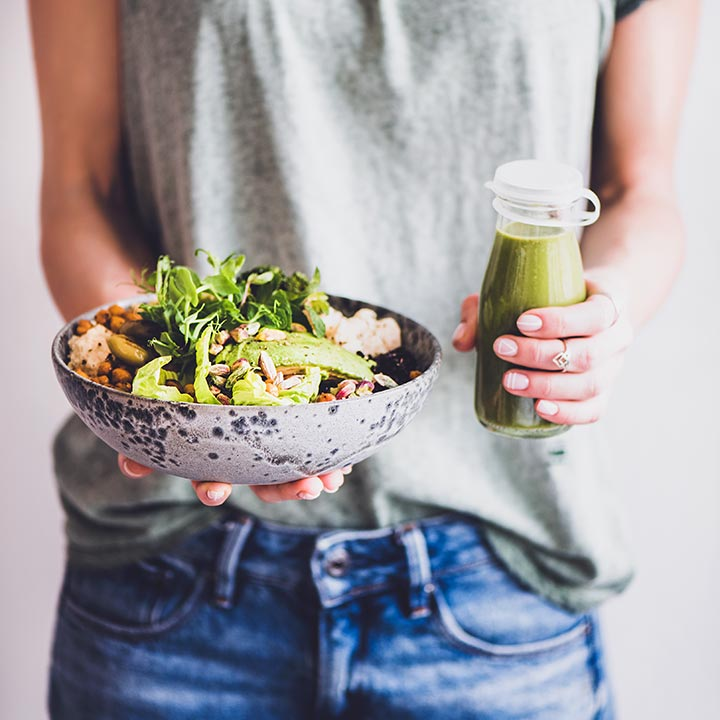Woman with green shirt standing and Holding a bowl of plant-based food and a green Smoothie