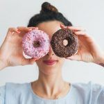 woman holding donuts in front of her eyes