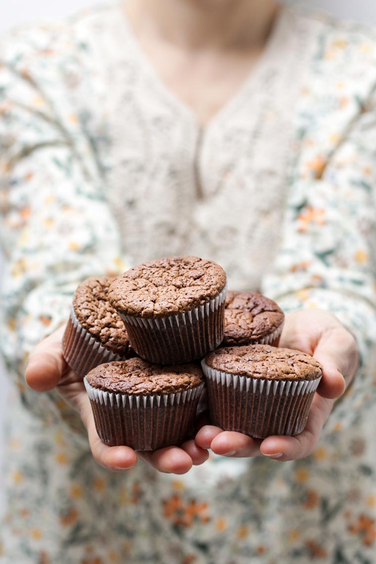 woman holding chocolate cupcakes in her hands