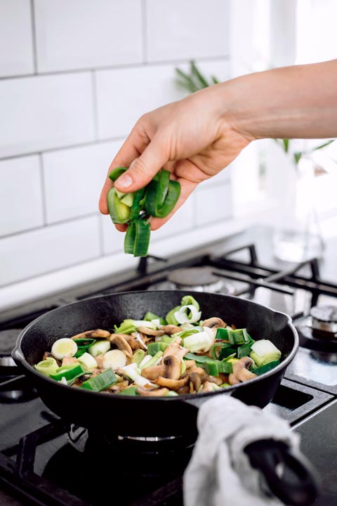 woman dropping freshly cut leek into pan of simmering mixed vegetables