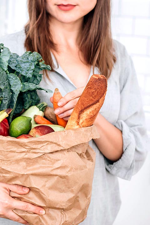 young woman holding paper bag full of vegetables, fruits and baguette in a bright kitchen