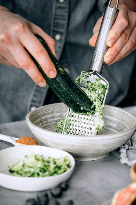 woman using a grater to shred zucchini into a beautiful ceramic bowl