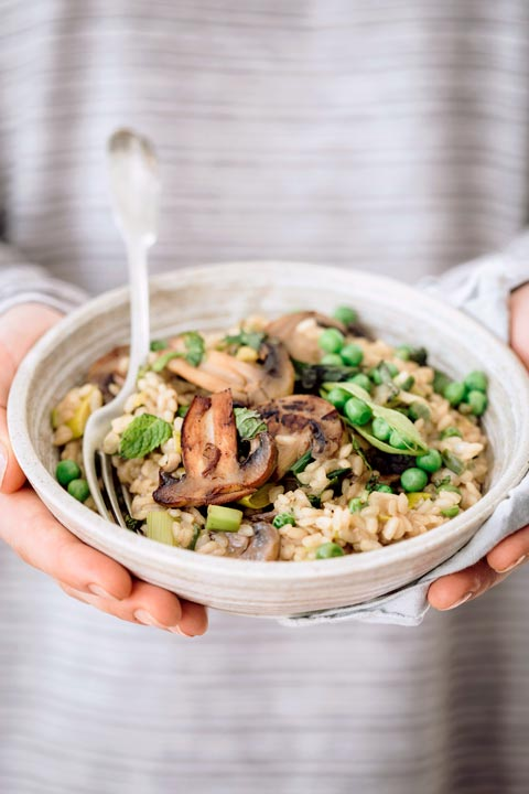 woman with grey stripe pullover holding risotto bowl with rice peas and mushrooms in her hands