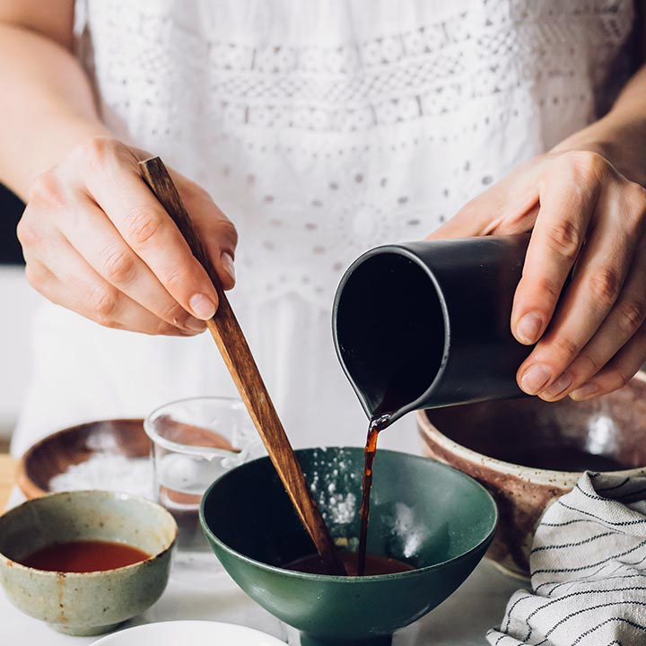 woman with beautiful white summer dress pouring soy sauce from jar into another bowl while whisking the sauce with chopsticks