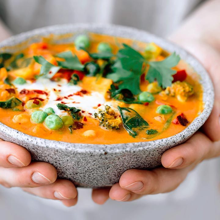 woman holding a grey bowl of orange vegan curry with coconut cream in her hands