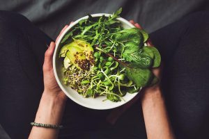 woman in black leggings sitting cross-legged and holding a white bowl of leafy greens, sprouts and avocado in her hands