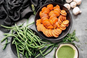 two black bowls filled with green beans and sweet potatoes standing on a stone surface next to some mushrooms and green sauce