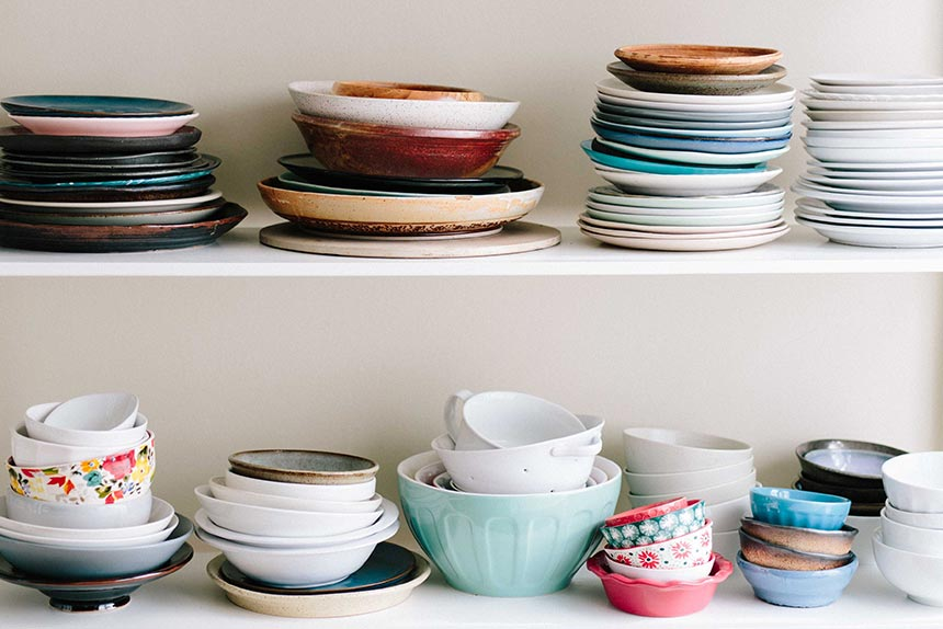 different colorful plates and bowls as part of more kitchen tools standing on a shelf