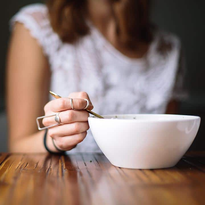 woman with white shirt and large rings on her fingers sitting on a table and eating out of a white bowl