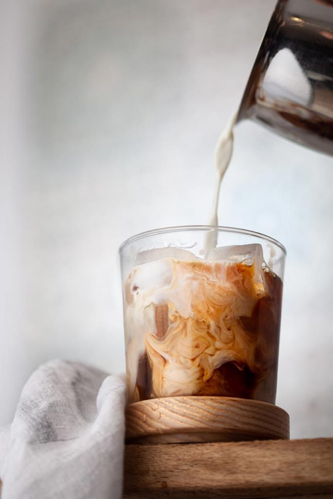 pouring soy milk in a glass of cold coffee with ice cubes standing on a wooden table
