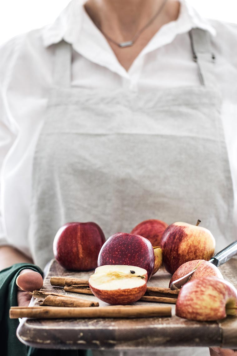 Woman in grey apron Holding Cutting Board With Apples, cinnamon and a knife
