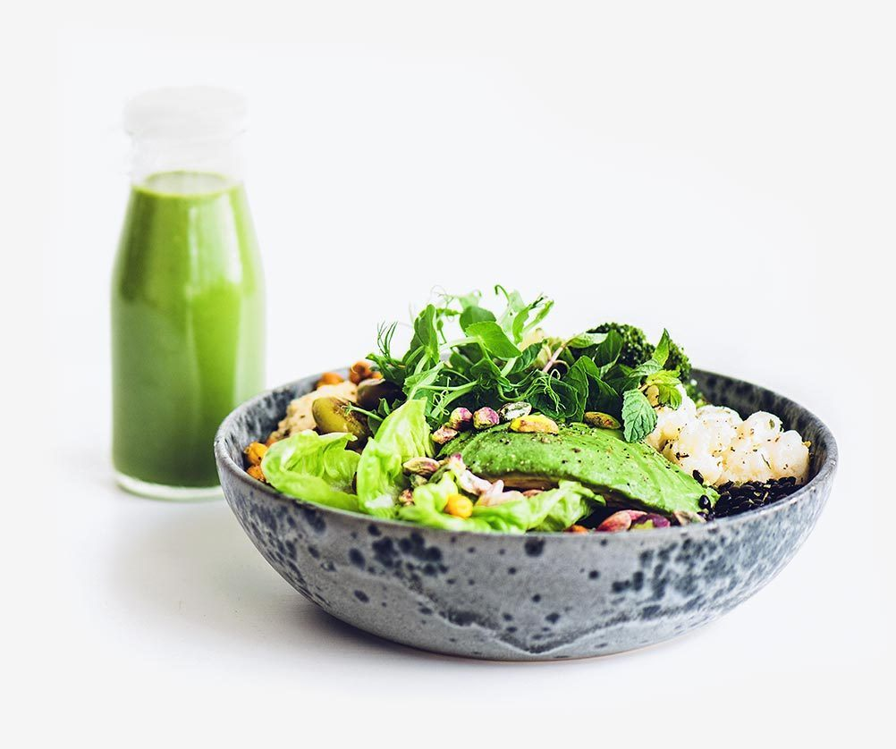 dark grey spotted bowl with a variety of vegetables next to small bottle of green smoothie isolated on light background