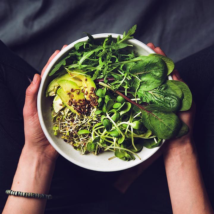 top view of woman holding a white bowl with spinach, avocado, arugula and sprouts inside