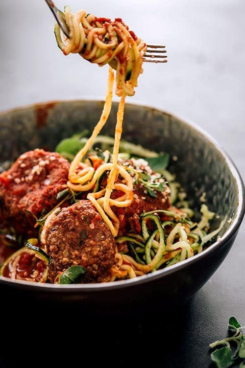 zucchini noodles rolled around fork over bowl of spiralized zoodles with black bean meatballs and marinara sauce