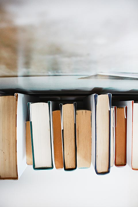 top view of a variety of books of different shapes and sizes standing on a white surface next to a window
