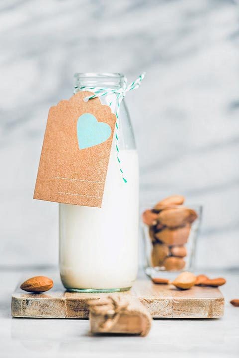 bottle of almond milk with brown label and small glass of almonds unfocused in the background on wooden cutting board