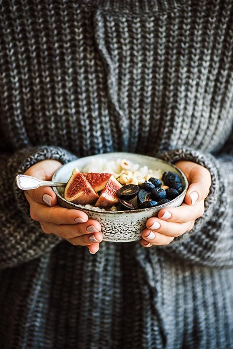 woman with cozy dark grey knitted sweater with hands wrapped around bowl of porridge topped with figs and blueberries