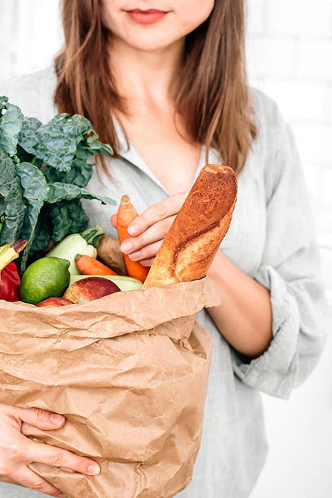 brown haired woman with linen shirt holding a paper bag with fresh produce and bread