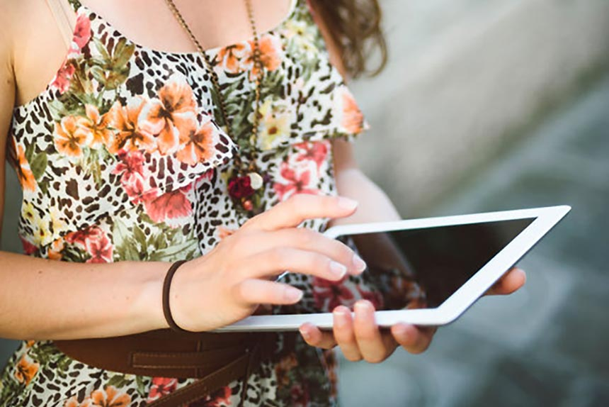 woman in floral dress standing with an ipad in her hand and scrolling with her finger